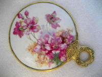 Victorian hand mirror with brass loop handle and apple blossoms
