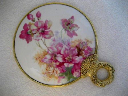Victorian Art Nouveau porcelain backed hand mirror with brass loop handle and apple blossom artwork